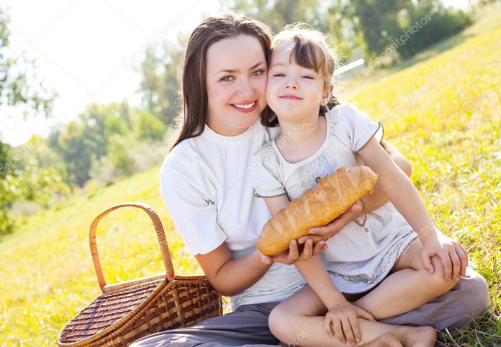 Beautiful young mother and her daughter having picnic in the park on a sunny autumn day — Stock Photo #3860862