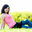 Young happy girl lying on grass — Stock Photo