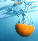 Fresh orange into blue, clear water — Stock Photo