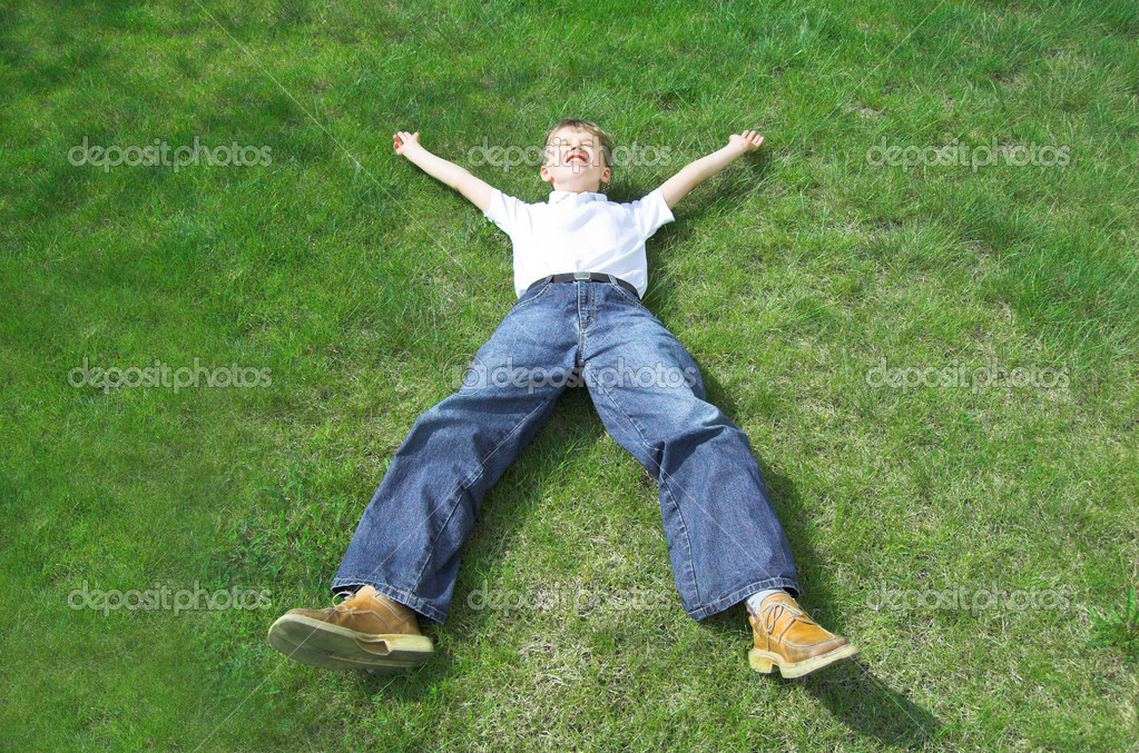 Happy boy lies on green grass. — Stock Photo #3481747