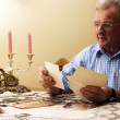 Senior man looking at old photographs. - Stock Photo