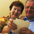 Senior couple looking at old photographs. — Stock Photo