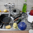 Foto Stock: Pile of dirty dishes in metal sink