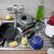 Pile of dirty dishes in the metal sink — Stok fotoğraf
