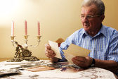 Senior man looking at old photographs. — Stock Photo