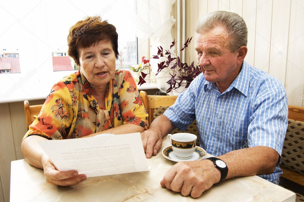 Senior couple signing document in home — Stock Photo #3510232
