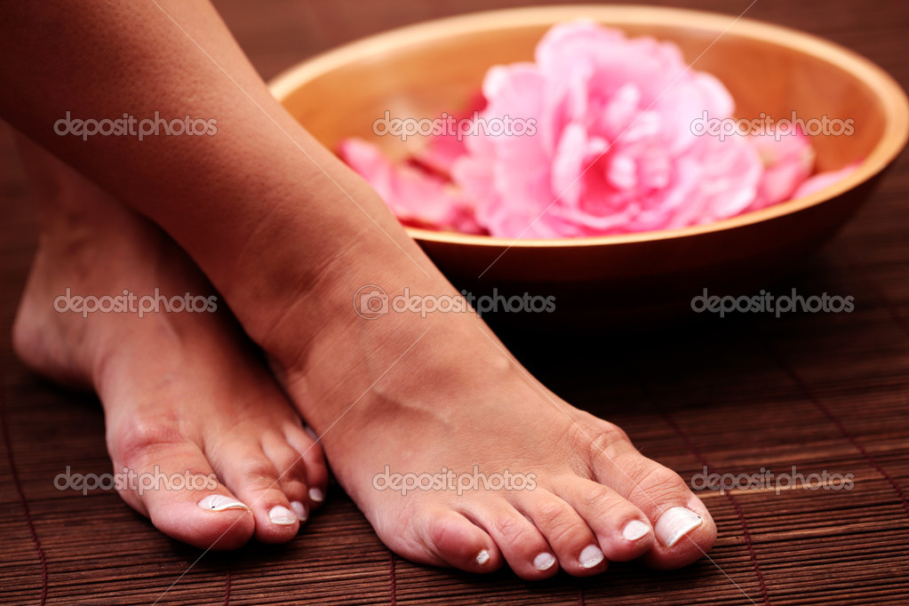 Sexy female feet with bowl of flowers - beauty treatment — Stock Photo #4570875