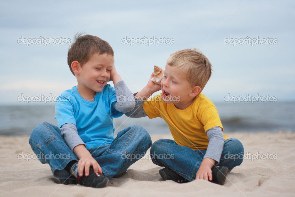 Two boys with shells on the beach - summertime — Stock Photo #4621931