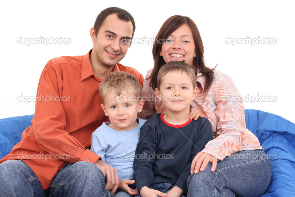 Mother father and two sons on the sofa - happy family — Zdjęcie stockowe #4667545