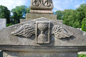 Sandglass with wings at a cemetery — Stock Photo
