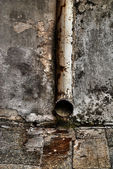 Rusty water pipe on grunge wall — Stock Photo