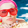 Beautiful woman with red sunglasses in the pool — Stock Photo