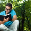 Young man reading book in the park — Stok fotoğraf