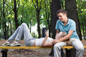 Young couple reading book in the park — Stock Photo