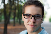 Portrait of young man in glasses standing outdoor — Stock Photo