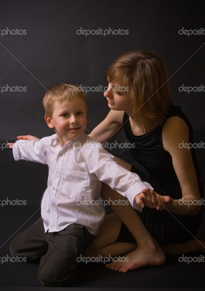 Portrait of a couple in studio with black background - mother helping her little son to hold his arms open — Stock Photo #2721193