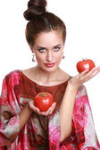 Charming girl with a tomato in hands — Stock Photo