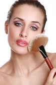 Beautiful woman with a make-up brush. — Stock Photo