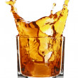 Glass with splashing whisky drink — Stok fotoğraf