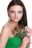 Portrait of a beautiful young woman with peacock feather — Stock Photo