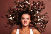 Vrouw en bloemblaadjes — Stockfoto