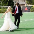 Wedding couple playing football — Stock Photo