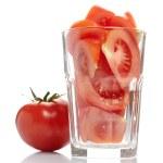 Tomato and tomato slices in glass — Stock Photo