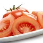 Tomato and tomato slices on white plate — Stock Photo