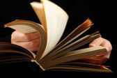 Looking thruogh book with motion blur on black background — Stock Photo