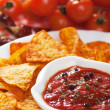 Tortilla chips with hot salsa dip - Stock Photo