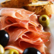 Prosciutto di Parma with olives — Stock Photo