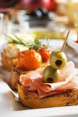 Bruschetta with prosciutto and olives — Stock Photo
