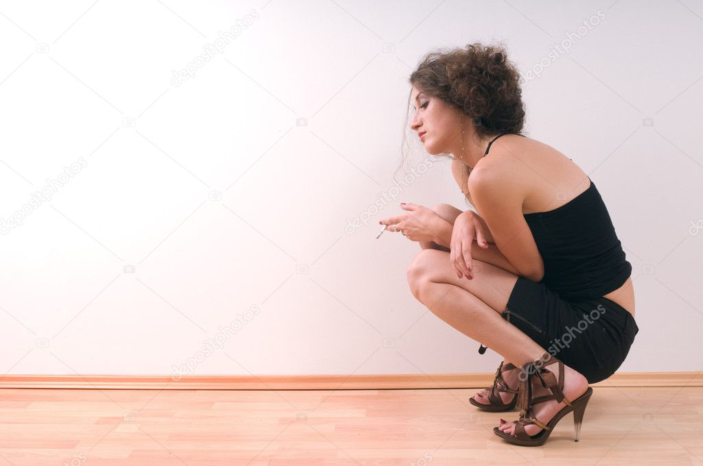 Lonely woman absorbed in thought with cigarette kneel beside wall  Stock Photo #2797505