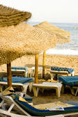 Straw umbrella and chairs — Stock Photo