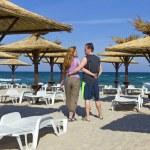 Beach ,beach umbrellas and young couple — Stock Photo