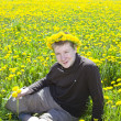 Teenager on meadow with dandelions — Stok fotoğraf