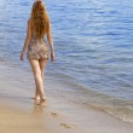 Graceful woman goes on coast of ocean — Stock Photo #3084020