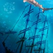 Sinking ship on sea bottom  and sharks - Stock Photo