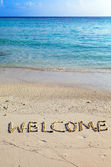 """Word """" welcome """" is written on sand on oceanside — Stock Photo"""