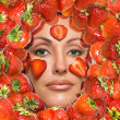 Portrait of young woman, laying under strawberry - Stock Photo