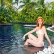 Young pretty woman in pool in tropical garden — Stock Photo