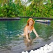 Young pretty woman in pool in tropical garden — Stock Photo #3525440