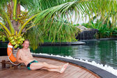 Man under palm tree at pool. Maldives. — Stock Photo