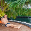 Sports man under palm tree at pool. Maldives. — Stock Photo