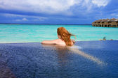 Woman in the pool and ocean in the background. Maldives — Stock Photo