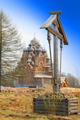 Cross before Wooden orthodox church in name of Cover All-holy mother of God — Stock Photo