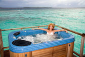 Woman in jacuzzi on background of ocean — Stock Photo