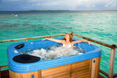 Pretty woman in jacuzzi on background of ocean — Stock Photo