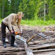 Woman in wood saws a tree a chain saw — Stock Photo