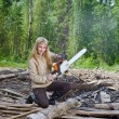 Woman in wood saws a tree a chain saw - Stockfoto